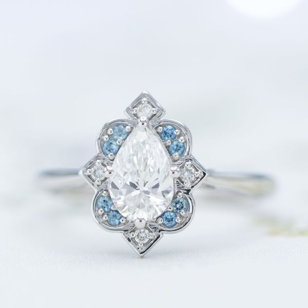A pear cut center stone in an Art Deco-inspired antique frame halo with aquamarines and diamonds.