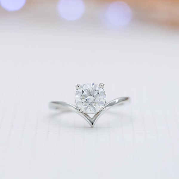 On its own, the engagement ring cradles the center diamond in an understated, modern setting.