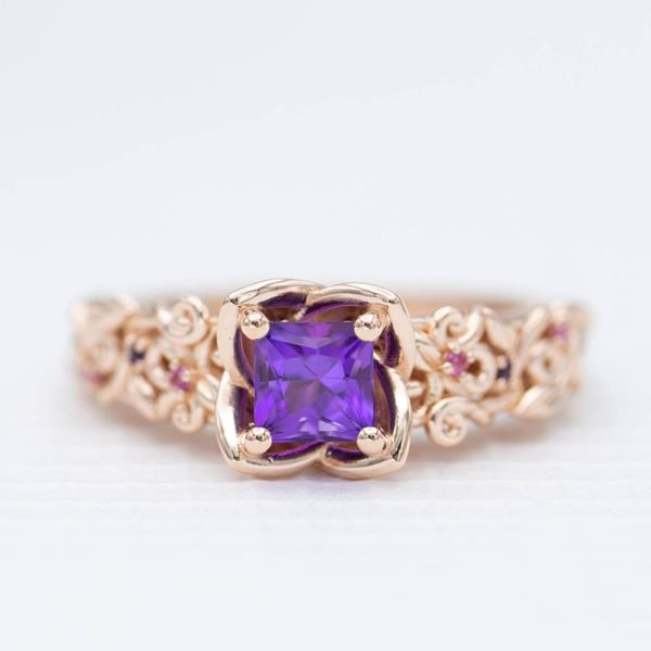 A custom-cut princess amethyst with a touch of red set in a flower-inspired ring with an intricately vining band.