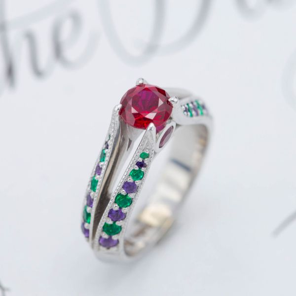 A center ruby and side peekaboo rubies held delicately by a split knife shank with unique amethyst and emerald accents.