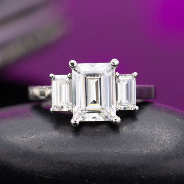 Geometric 3-stone ring with emerald cut moissanites.
