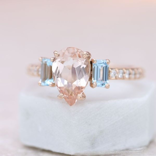 Aquamarine accents help highlight the beauty of the pear shape morganite center stone.
