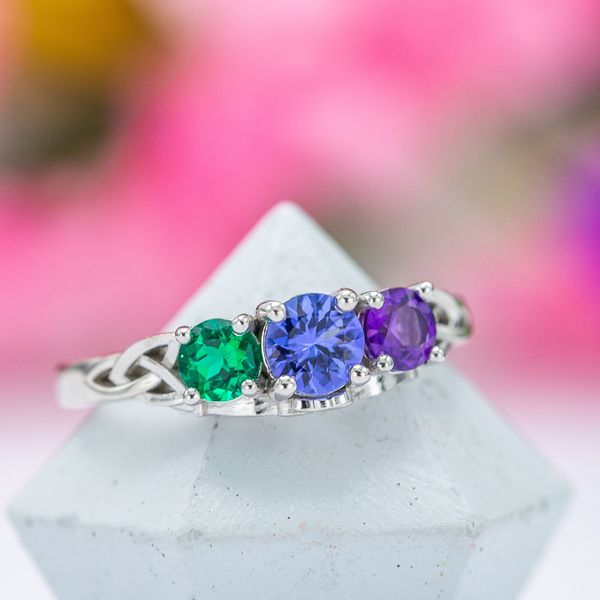A Celtic trilogy ring with amethyst and emerald around the tanzanite center stone.