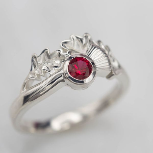 Designed to match the earrings he first bought for her, this design sets asymmetric leaf detail around the ruby center stone.