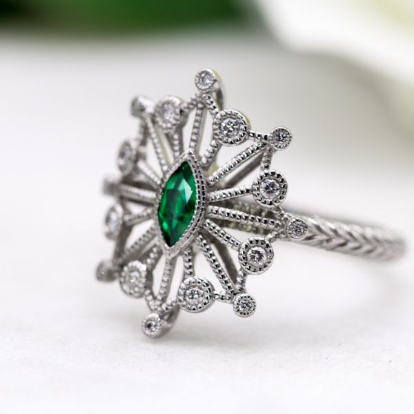 A snowflake-inspired setting with repeating chevrons on the band and a bright pop of emerald in the marquise cut center stone.