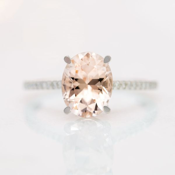 A perfectly delicate diamond pave band offsets the bright peach-pink morganite center stone. The flat finish to the tapered prongs reinforces the ring's modern aesthetic.