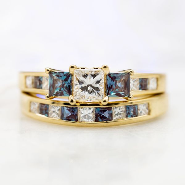 Clean, contemporary bridal set in yellow gold with channel set diamonds and alexandrite accents surrounding the three stone princess cut center setting.