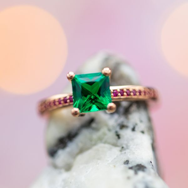 Modern styling for this engagement ring with a princess cut emerald and ruby accents.