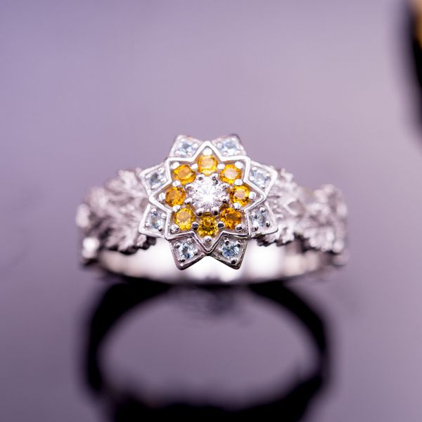 A cluster of citrine, aquamarine and diamonds adds color to the petals of this flower engagement ring.
