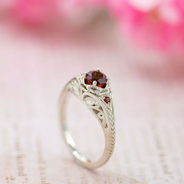 Vintage-inspired garnet engagement ring with floral setting and Deco-inspired chevron band.