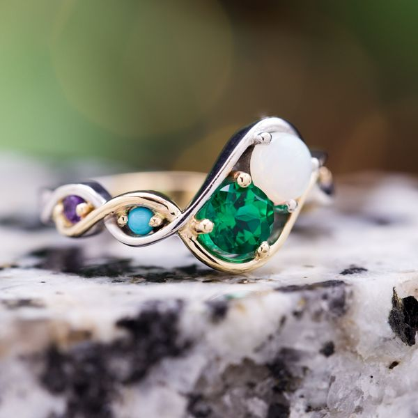 "His goal: ""a ring with a theme of harmony and joining of families."" The toi-et-moi two-stone setting of emerald and opal represents their union, reinforced by the intertwined yellow and white gold bands. Accents of turquoise, peridot, amethyst and emerald represent the families."