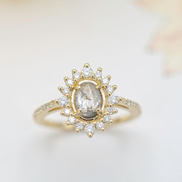 A salt and pepper, rose cut diamond is framed by a gold sunburst halo for a unique engagement ring design.