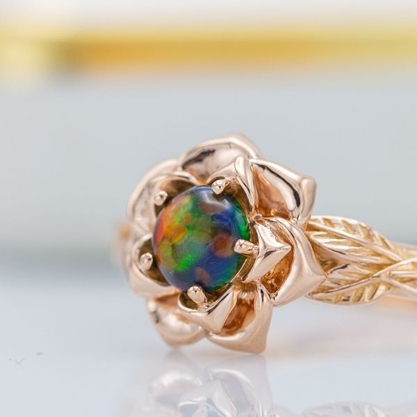 A lab-made opal shows its vivid blues, greens and oranges at the heart of this rose engagement ring.