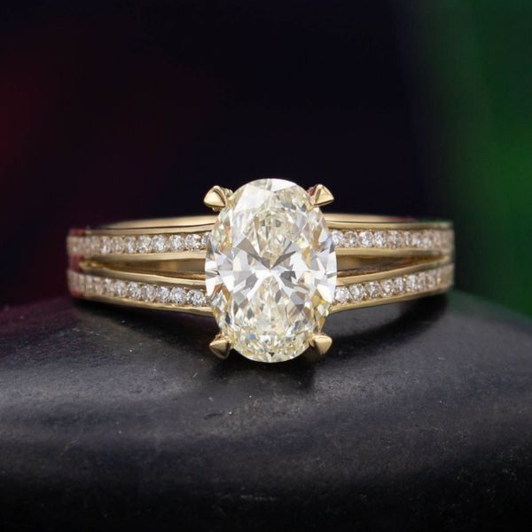 1.29 carat oval diamond in a split shank yellow gold engagement ring with channel set pave diamonds.