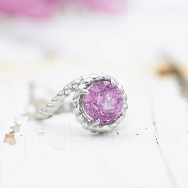 Pink spinel ring with a rope band in a bypass setting.