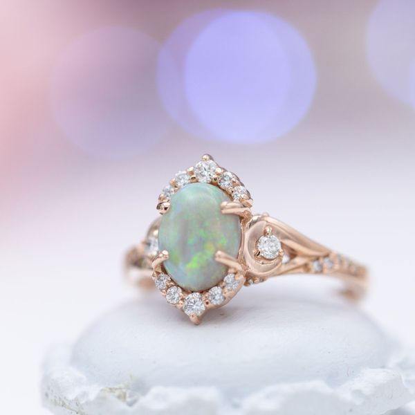An elegant, vintage-inspired engagement ring featuring the blue-green shimmer of opal as its center stone.