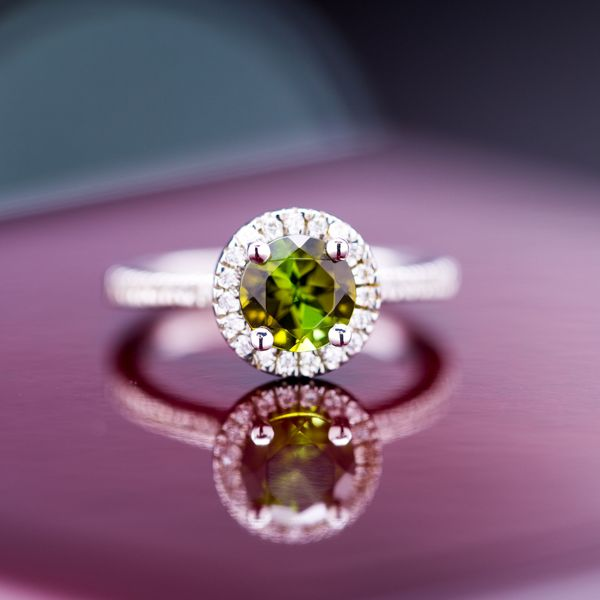 A modern engagement ring in white gold with a deep green tourmaline surrounded by a diamond halo.