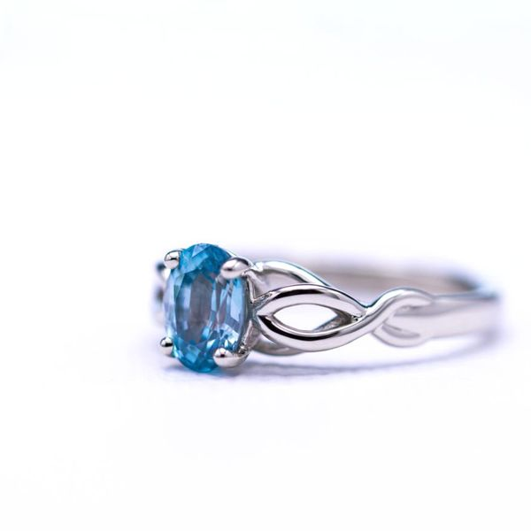 Engagement ring with vining rope detail and oval blue zircon center stone.