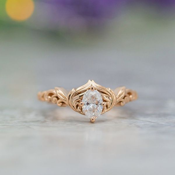 Delicate, curvy engagement ring in rose gold with feathers framing an oval diamond.