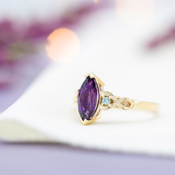 Marquise cut amethyst engagement ring with twisting gold band an diamond accents.