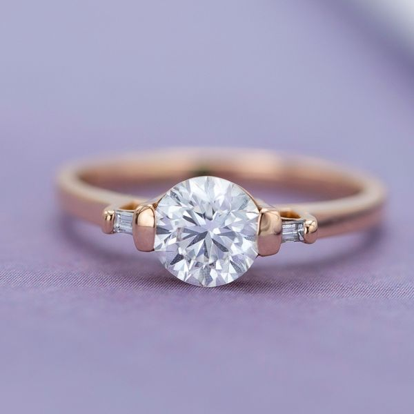 This three stone engagement ring uses bright, open bar settings for the round center stone and baguette side stones.