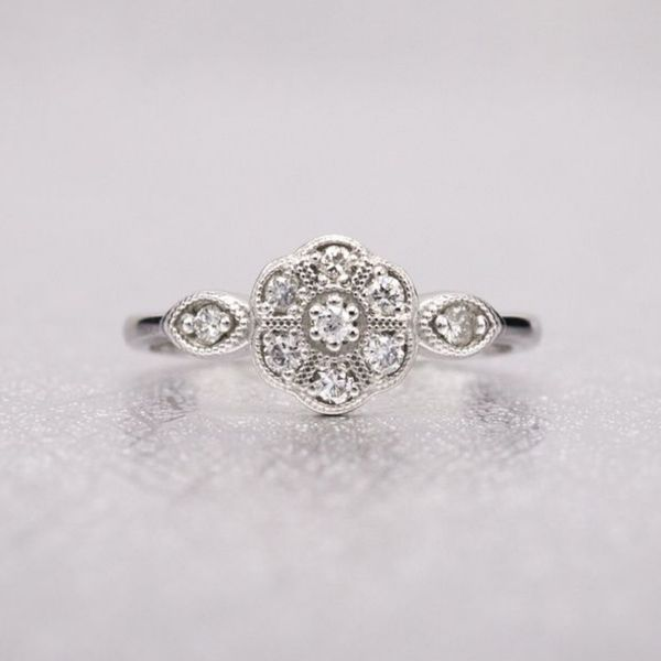 This delicate, vintage-inspired ring sets multiple small diamonds in a floral setting with milgrain edging.