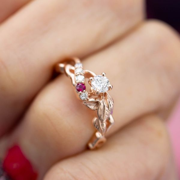 A nature inspired look adds a row of ruby and diamond accents to balance a smaller diamond center stone.