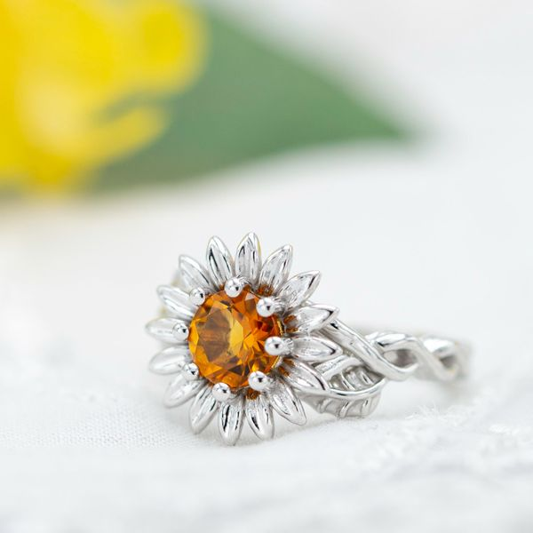Citrine sunflower engagement ring with vining band, sculptural leaf and petal setting.
