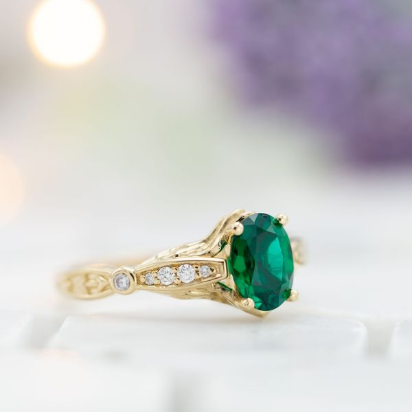 Emerald engagement ring with vintage-style band detailing.