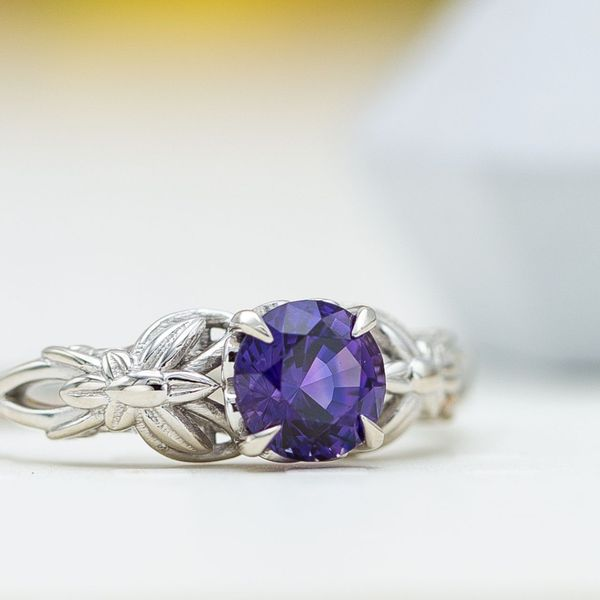 A nature-inspired white gold engagement ring with a royal purple sapphire center stone.