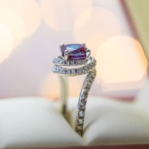 An elegant curve of diamonds spirals around and up to create the setting for a cushion cut alexandrite.