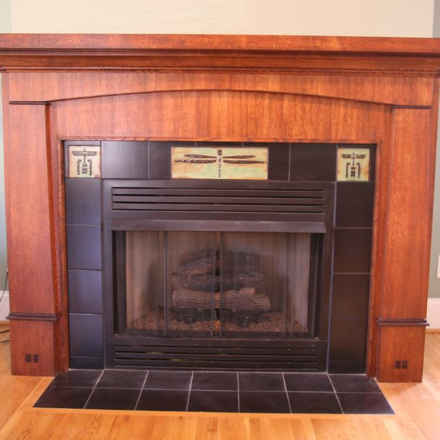 This custom fireplace mantle and surround was designed in the Craftsman style and features quartersawn white oak that is stained and glazed to give a …