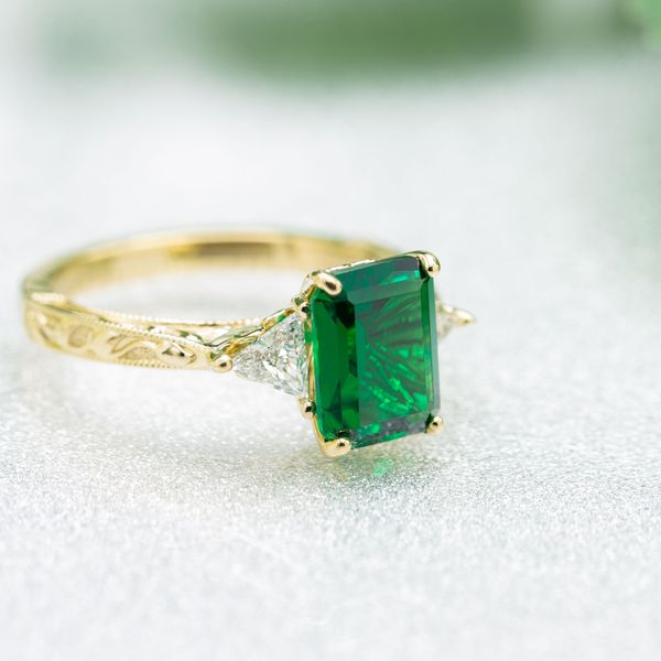 This emerald cut showcases the vibrant green of the emerald center stone in this classic gold setting.