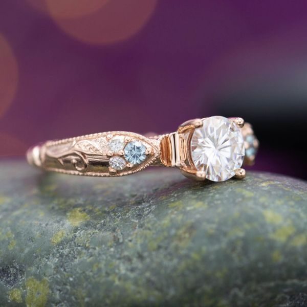Vintage-inspired rose gold and moissanite engagement ring. Shield-shaped shoulders with leafy details and aquamarine accents.