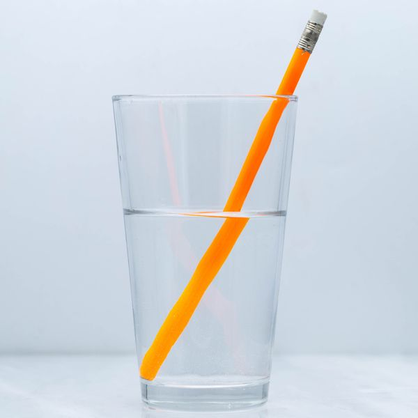 Light moves at different speeds through air and water, creating the illusion that the pencil bends at the water line. The same phenomenon causes light to bend as it travels through a gemstone.