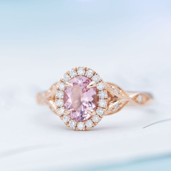 A beautiful halo engagement ring with diamonds surrounding the morganite center stone.