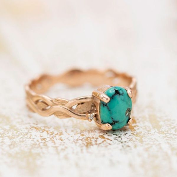 A bohemian engagement ring, with earthy rose gold and green-hued turquoise webbed with beautiful black veining.