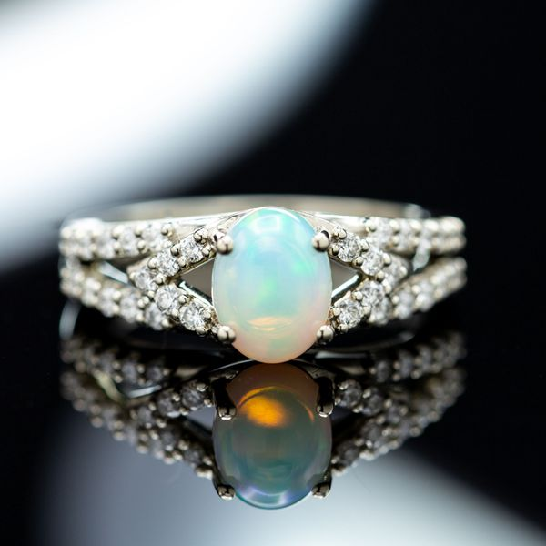 Split shank setting for a prong-set white opal cabochon with diamonds for sparkle.
