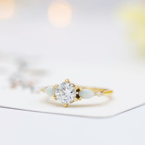 This engagement ring mixes diamond and white opal for a contrast of sparkle and subdued pastel color play.