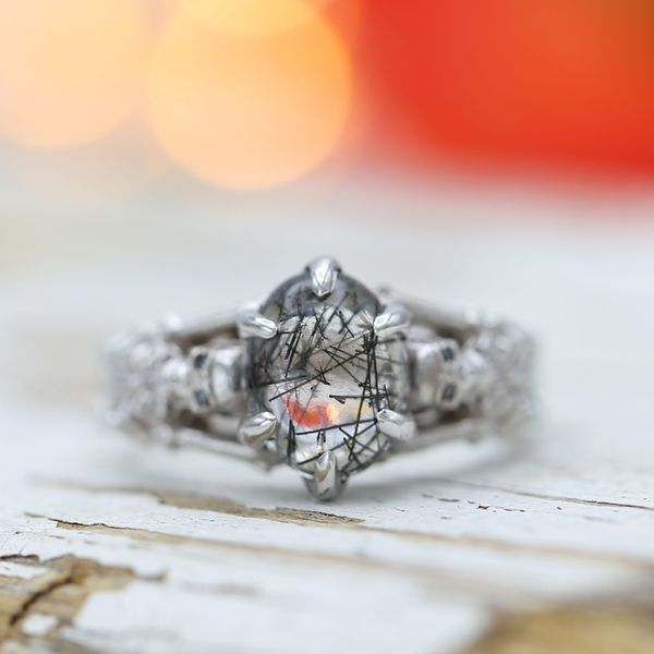 A skeleton engagement ring featuring the unique look of tourmalinated quartz at its center.