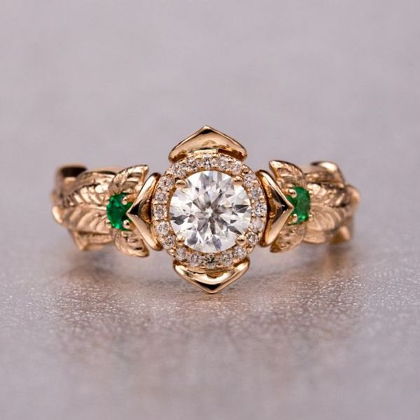 Designed in rose gold, this engagement ring features a diamond halo center setting tucked inside lotus petals. The shank features detailed, natural elements: textured bark and accent emeralds in the leaves on each shoulder of the ring.