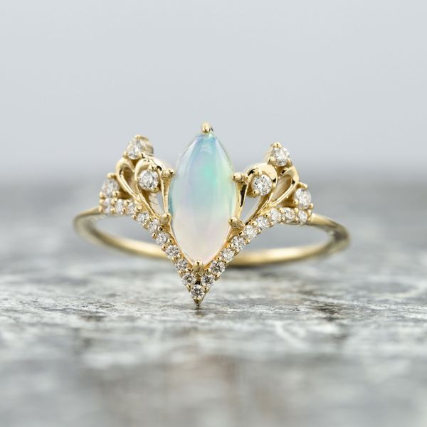 This opal and diamond ring has elegant curves and styling reminiscent of a vintage tiara.