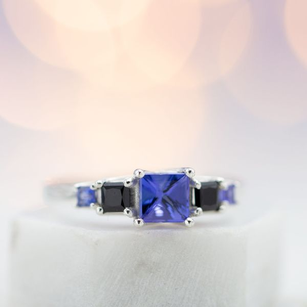 Five stone engagement ring with trellis-set princess cut tanzanite and black spinel.