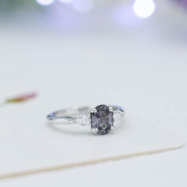 Gray spinel engagement ring with pear cut diamonds in a three-stone setting.