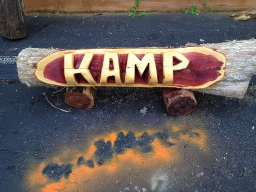 Hand crafted chainsaw carved name log canoe style by the