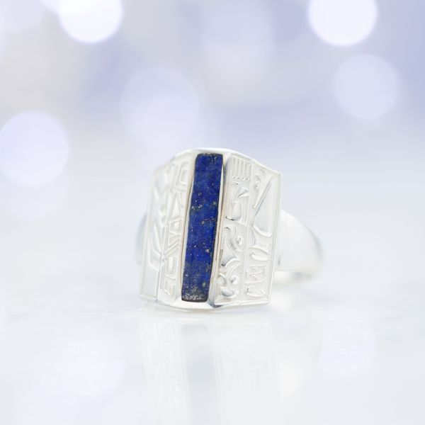 A unique lapis lazuli ring with tribal symbols engraved along the elongated face.