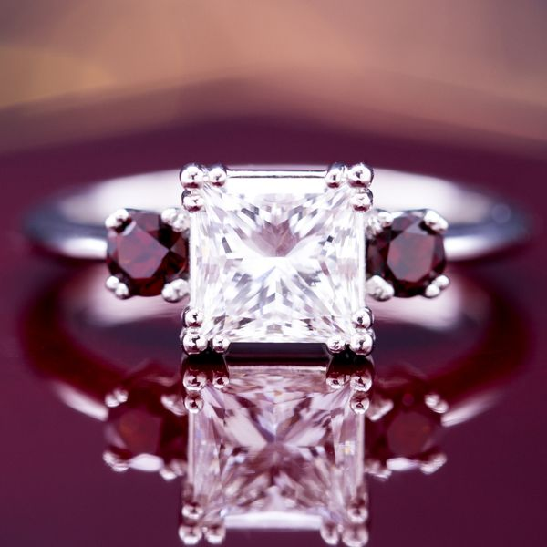 A large, princess cut center diamond gets a bright pop of burgundy red from Mozambique garnet side stones.