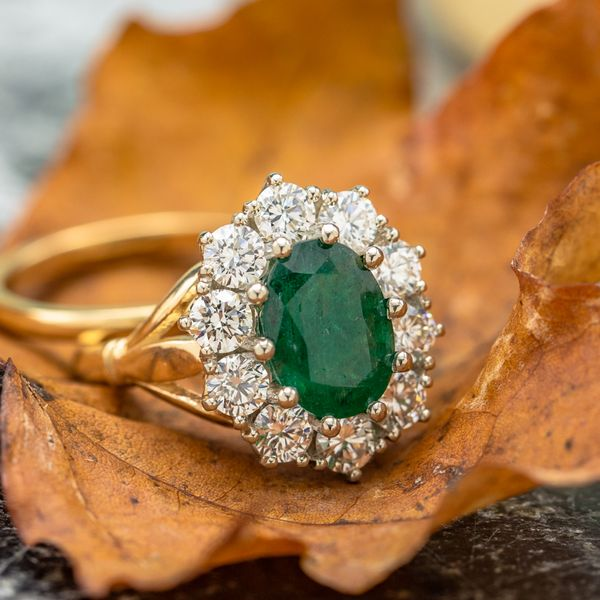 A beautiful 2.4ct oval emerald surrounded by a vintage-inspired yellow gold setting with a sunburst diamond halo.