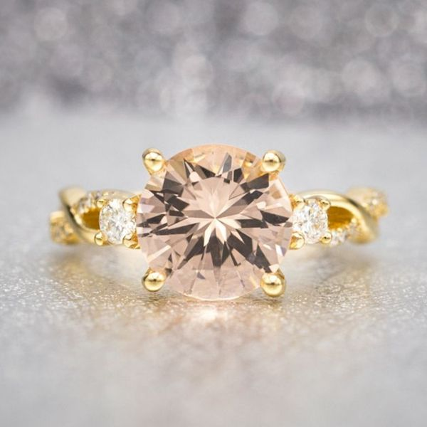 This ring's vining yellow gold setting draws out the warm tones of the round morganite center stone, and the proportion of the side diamonds ensures the center stone really pops.