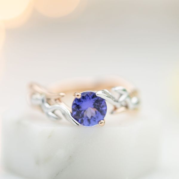 This modern ring mixes two tones of gold in a bypass setting for the purple-blue tanzanite center stone.